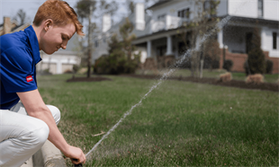 Young Technician Working On A Sprinkler