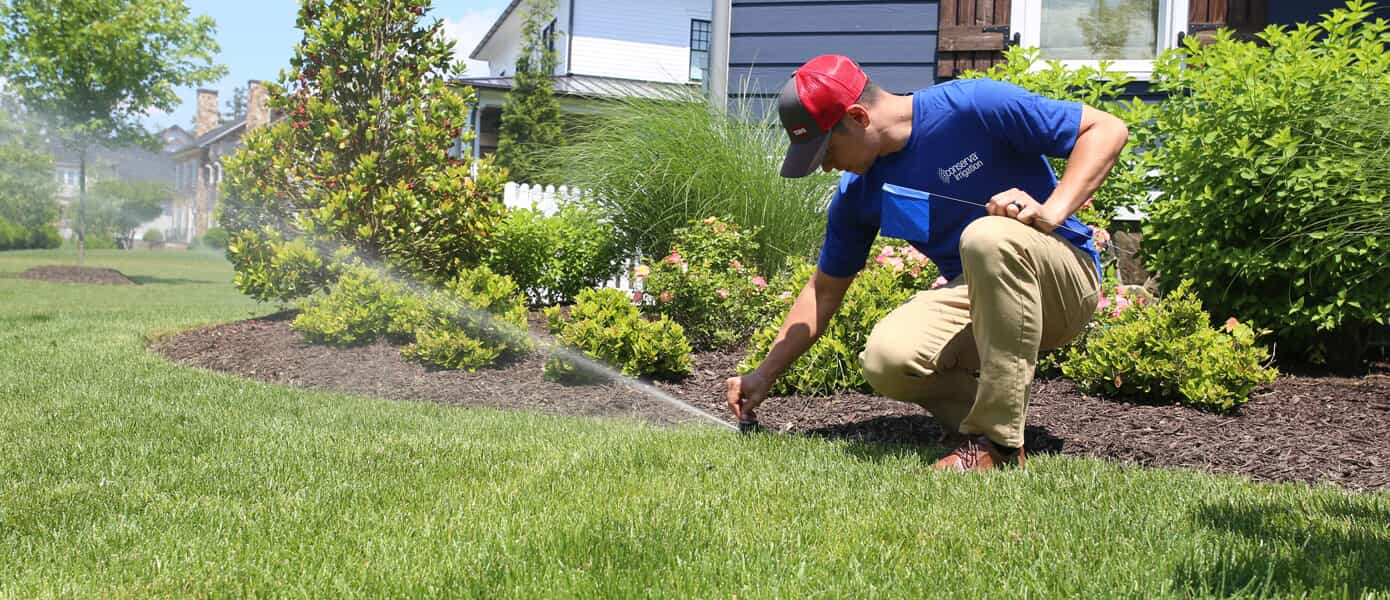 conserva irrigation employee doing routine maintenance on residential front lawn
