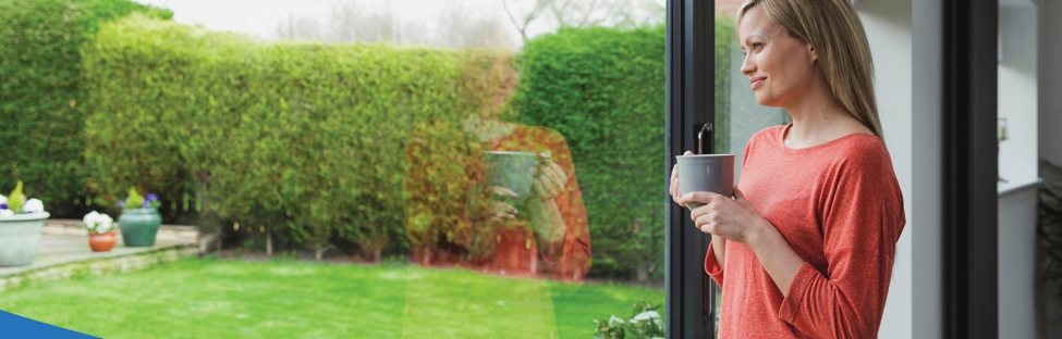 Blonde woman holding mug looking happily out her window at her green grass in the yard