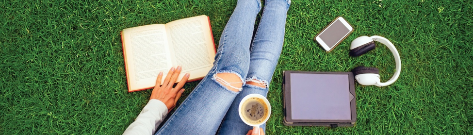 woman sitting on green grass with a book, mug, headphones, phone, and tablet